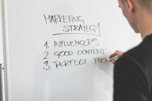 Marketing Expert Writing New Strategy on Whiteboard