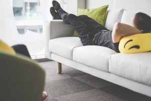 Young Man Napping on White Sofa in the Office